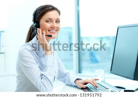 Portrait of young operator with headset looking at camera with friendly smile - stock photo