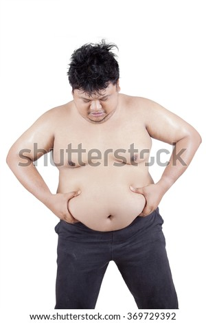 Portrait of young overweight person holding his big stomach in the studio, isolated on white background - stock photo