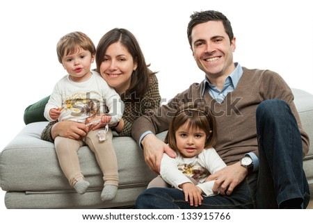 Portrait of young parents with their daughters on couch.Isolated. - stock photo