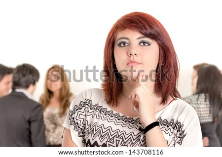 Portrait of young pensive asian woman with her business partners on the background - stock photo