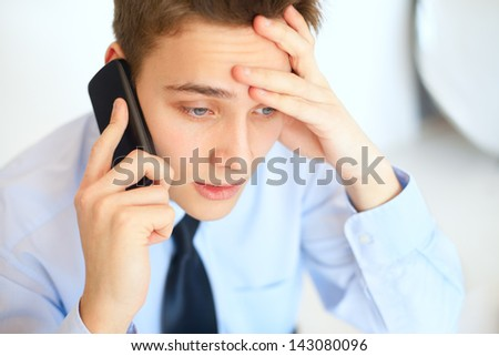Portrait of young pensive businessman talking on cell phone in office - stock photo