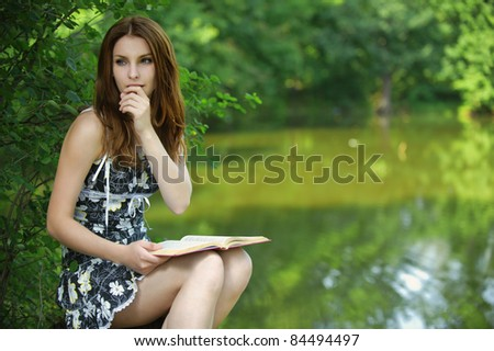 Portrait of young pensive girl holding book, wearing black dress at summer green park.