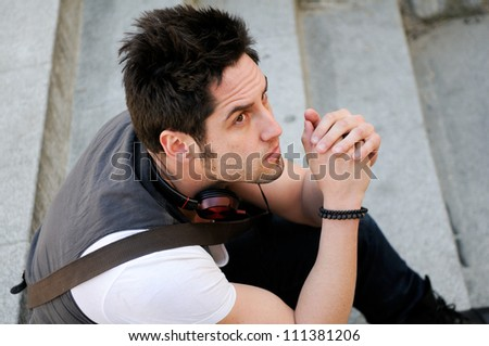 Portrait of young pensive man sitting on steps, with headphones - stock photo