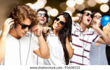 portrait of young people having a party against a golden lights