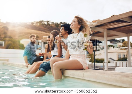 Portrait of young people sitting on the edge of the swimming pool with their feet in water. Friends relaxing by the pool during a party. - stock photo