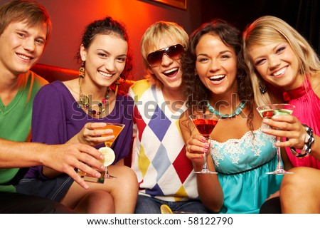 Portrait of young people with martini glasses laughing in the nightclub