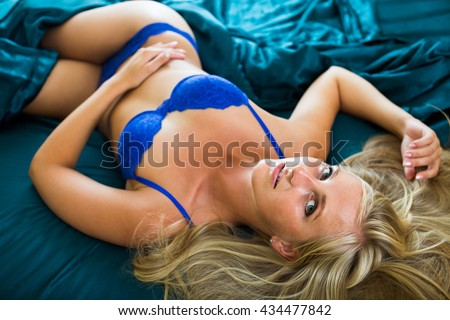 Portrait of young positive woman in sexy underwear indoors - stock photo