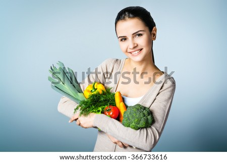 Portrait of young positive woman standing against grey background. Woman looking at camera and holding fresh vegetables. Concept for healthy food - stock photo