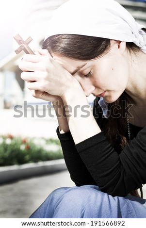 Portrait of young praying woman with closed eyes with wood cross in her hands - stock photo