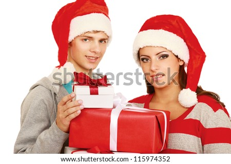 Portrait of young pretty couple holding big red box - christmas gift and looking at camera - stock photo