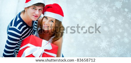 Portrait of young pretty couple standing indoors wearing Santa Claus helper hats and hugging. Holding big red box - christmas gift and looking at camera. Magical background with snowflakes. ?opyspace