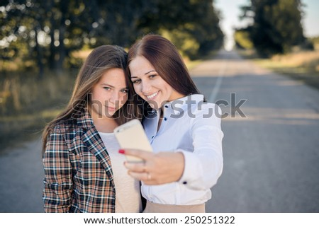 Portrait of 2 young pretty ladies enjoying making self image on summer countryside road - stock photo