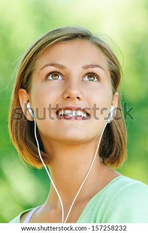 portrait of young, pretty, quiet woman with short hair in headphones, smiling, against backdrop of summer Nature - stock photo