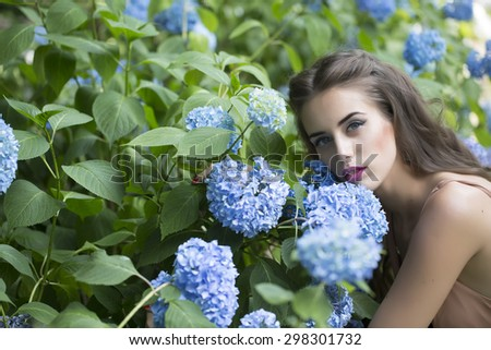 Portrait of young pretty sexual girl with bright makeup and long curly brunette hair sitting near lush bush with blue flowers of hydrangea and green leaves looking forward, horizontal picture - stock photo