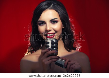 Portrait of young pretty singing woman on red background, close up