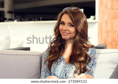 Portrait of young pretty smillng girl. Outdoor summer portrait. Beautiful brunette woman with long curly hair looking in camera - stock photo