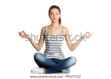 Portrait of young pretty student girl over white background meditating in lotus pose. She is relaxed and concentrated - stock photo