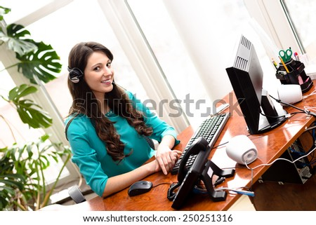 Portrait of young pretty woman call center operator speaking on headphones at work place with computer on light window background - stock photo