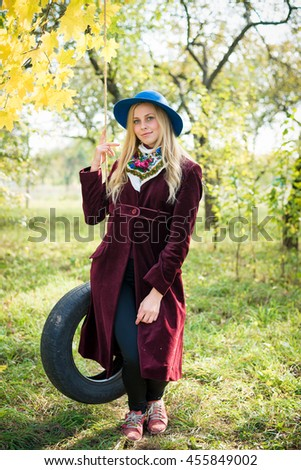 Portrait of young pretty woman having fun on swing on sunny autumn day outdoors copy space background