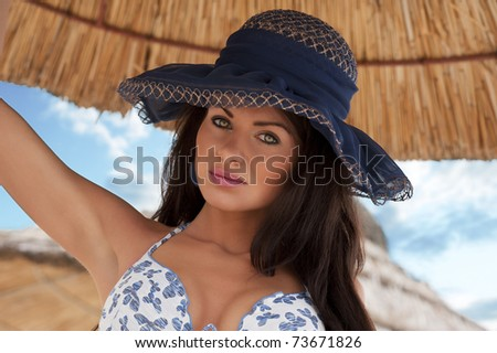 portrait of young pretty woman in bikini with a blue hat with sky in background - stock photo