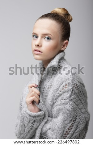 Portrait of Young Pretty Woman in Knitted Woolen Gray Jersey - stock photo