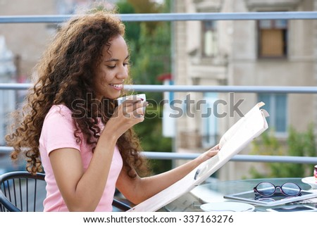 Portrait of young pretty woman reading newspaper at summer terrace in the town - stock photo