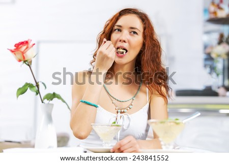 Portrait of young pretty woman sitting at cafe and eating dessert
