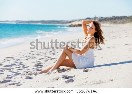 Portrait of young pretty woman sitting on the beach