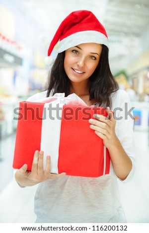 Portrait of young pretty woman wearing Santa Claus helper hat standing inside shopping mall smiling and holding christmas gift - stock photo