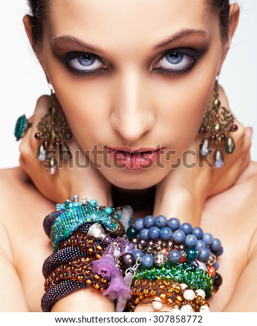 Portrait of young pretty woman with bijouterie on hands looking in camera