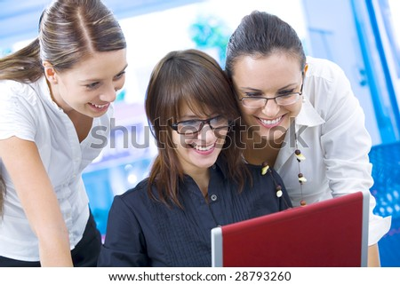 Portrait of young pretty women discussing project in office environment