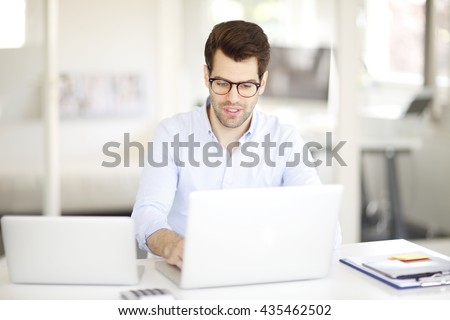 Portrait of young professional man sitting at office in front of laptop while working on presentation.