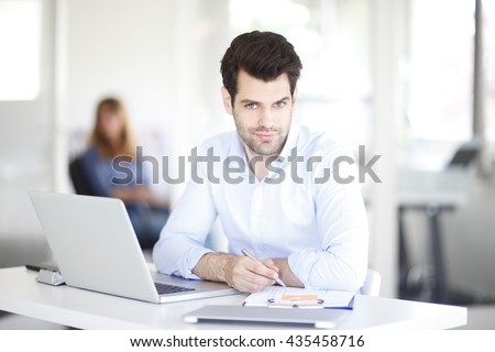 Portrait of young professional man working on laptop at office.