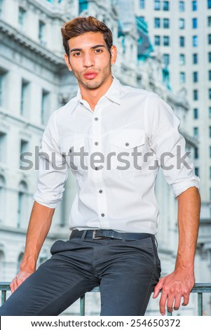 Portrait of Young Professional. Wearing a white shirt, sleeves rolling over, black pants, a young college student is sitting in the front of business district, confidently looking forward.  - stock photo