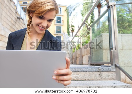 Portrait of young professional woman sitting on steps in city with classic buildings, smiling and using a laptop computer to work, sunny exterior. Business woman using technology outdoors, lifestyle. - stock photo