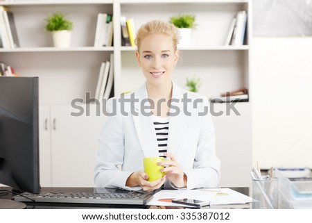 Portrait of young professional women sitting in front of computer at office and drinking tea while looking at camera and smiling.