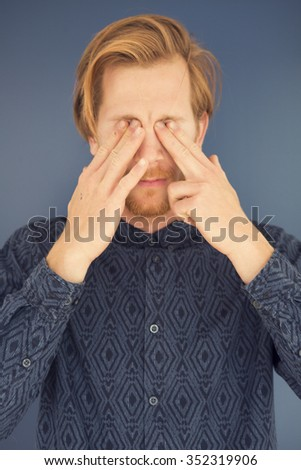 portrait of young red-haired man with beard having a headache - stock photo