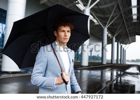 Portrait of  young redhaired businessman holding black umbrella in rainy street