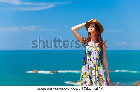 Portrait of Young redhead woman in a hat near the ocean - stock photo