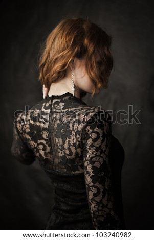 Portrait of young redhead woman in lace dress - stock photo