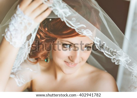 Portrait of young redheaded woman bride, through the wedding veil - stock photo