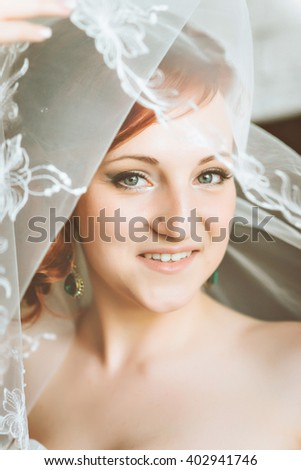 Portrait of young redheaded woman bride, through the wedding veil. Looking at the camera. - stock photo