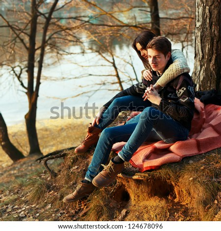 Portrait of young romantic couple sitting in forest enjoying themselves - Outdoor - stock photo