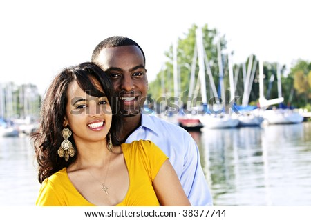 Portrait of young romantic couple standing at harbor - stock photo