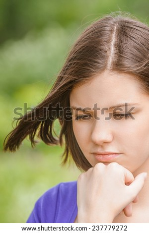 Portrait of young sad dreamy brunette woman wearing violet blouse and propping up her face at summer green park. - stock photo
