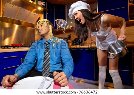 Portrait of  young sad falling out a couple (male, female) background of kitchen - stock photo