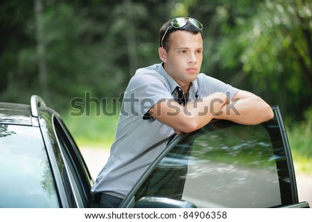 Portrait of young sad pensive man wearing sunglasses standing near car. - stock photo