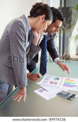 Portrait of young sales persons studying their results in an office - stock photo