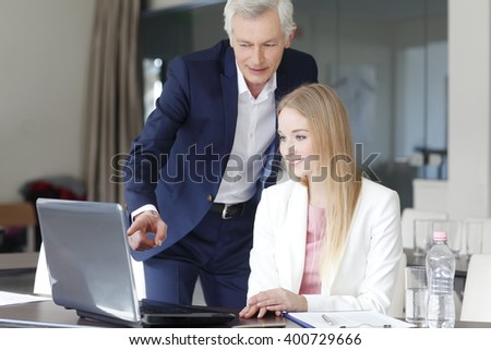 Portrait of young sales woman sitting in front of laptop and consulting with senior businessman while working on laptop at office.