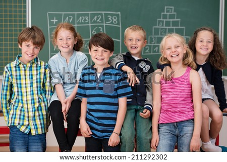 Portrait of young school children in class posing in a row together in front of the blackboard laughing at the camera - stock photo